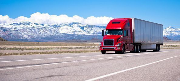 transport truck driving along highway red cab